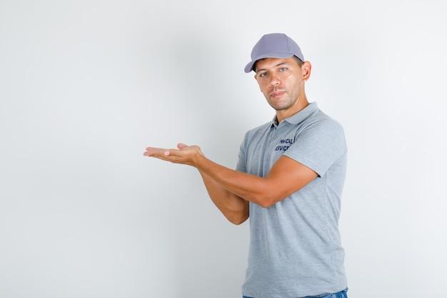 Uomo di servizio tecnico in maglietta grigia con cappuccio che tiene insieme i palmi aperti Foto Gratuite