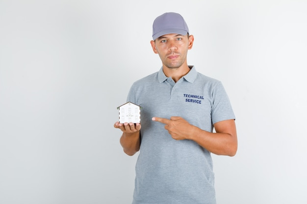 Technical service man in grey t-shirt with cap showing house model with finger Free Photo