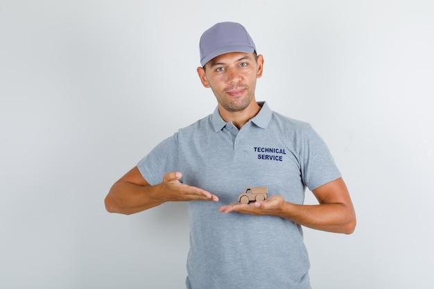 Uomo di servizio tecnico in maglietta grigia con cappuccio che mostra macchinina in legno Foto Gratuite