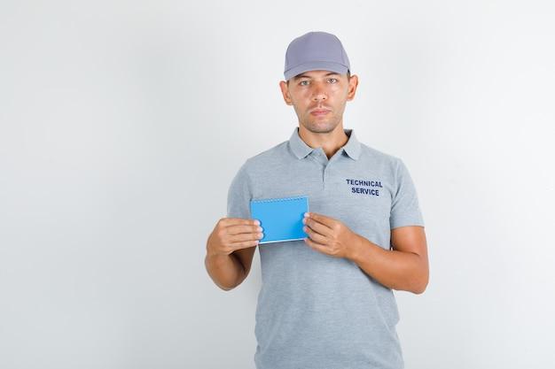 Uomo di servizio tecnico che tiene mini taccuino in maglietta grigia con cappuccio Foto Gratuite