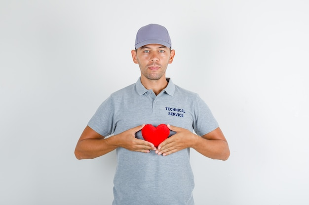 Uomo di servizio tecnico che tiene cuore rosso in maglietta grigia con cappuccio Foto Gratuite