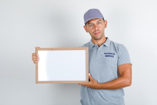 Uomo di servizio tecnico che tiene scheda bianca in maglietta grigia con cappuccio, vista frontale. Foto Gratuite