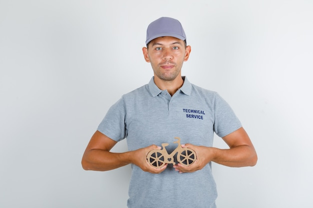 Technical service man holding wooden toy bicycle in grey t-shirt with cap, front view. Free Photo