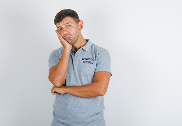 Technical service man leaning his cheek on raised palm in grey t-shirt and looking upset Free Photo