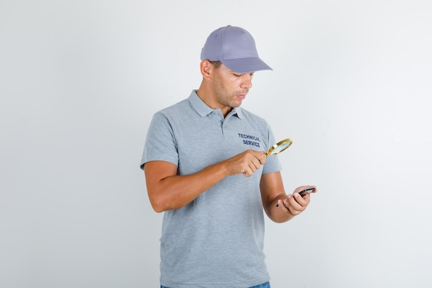 Technical service man looking smartphone over magnifying glass in grey t-shirt with cap Free Photo