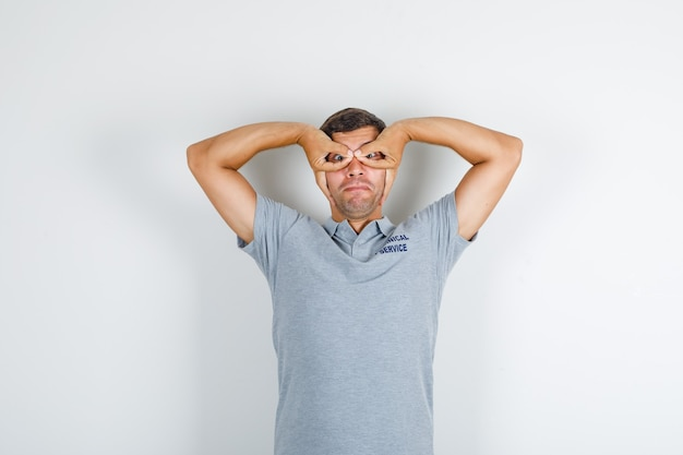 Technical service man showing glasses gesture in grey t-shirt and looking funny Free Photo