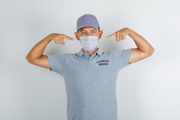 Technical service man showing medical mask in grey t-shirt with cap and looking careful Free Photo
