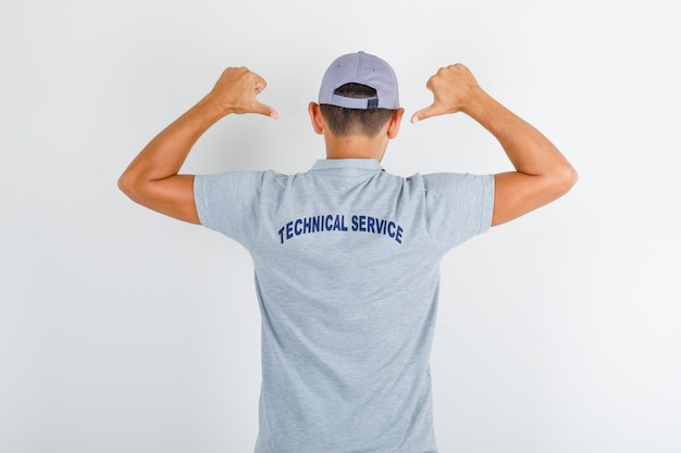 Technical service man showing text on uniform in grey t-shirt with cap Free Photo