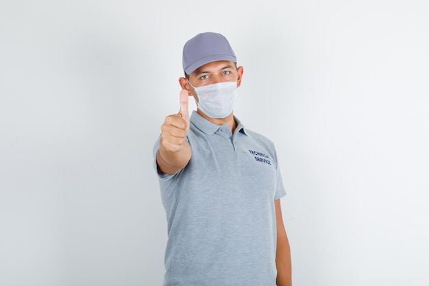 Technical service man showing thumb up in grey t-shirt with cap and medical mask and looking careful Free Photo
