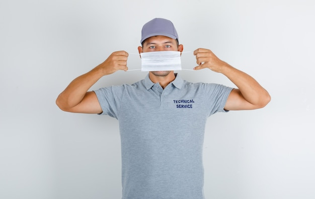 Technical service man wearing medical mask in grey t-shirt with cap and looking careful Free Photo