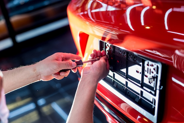 Technician changing car plate number in service center. Premium Photo