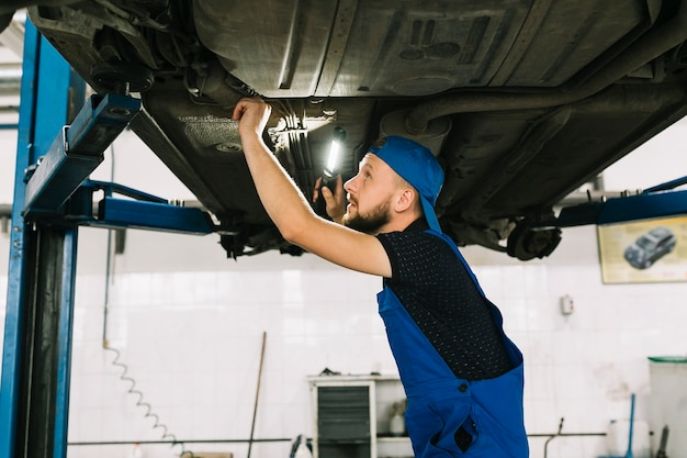 Technician checking vehicle bottom Free Photo