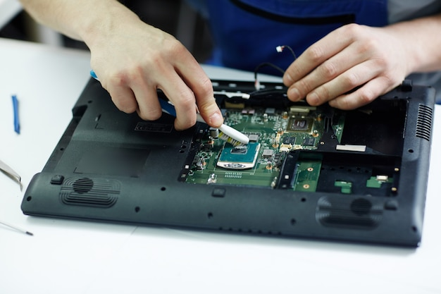 Technician clearing circuit board of disassembled laptop Free Photo