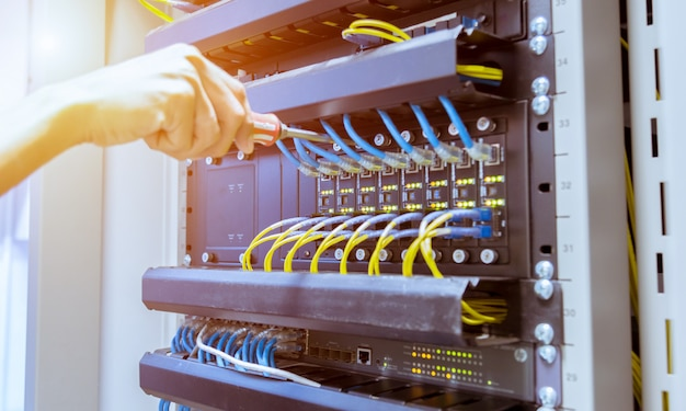 Technician connecting network cable to switch Premium Photo