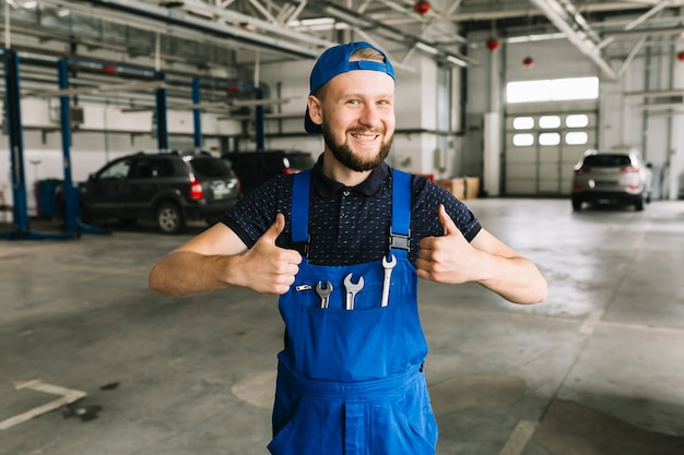 Technician in coveralls with wrenches at workshop Free Photo