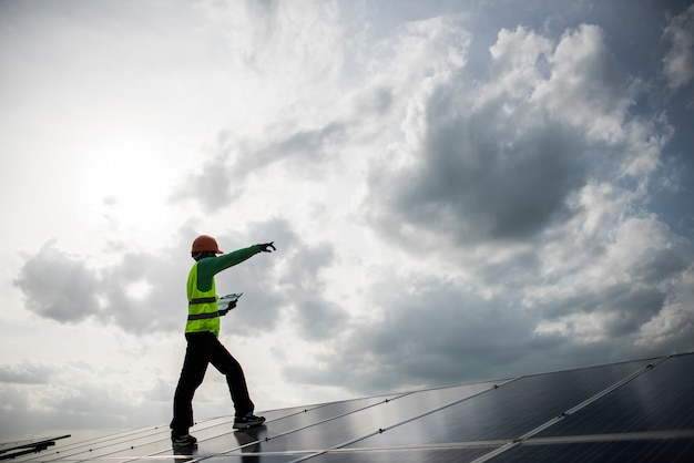 Technician engineer checks the maintenance of the solar cell panels. Free Photo