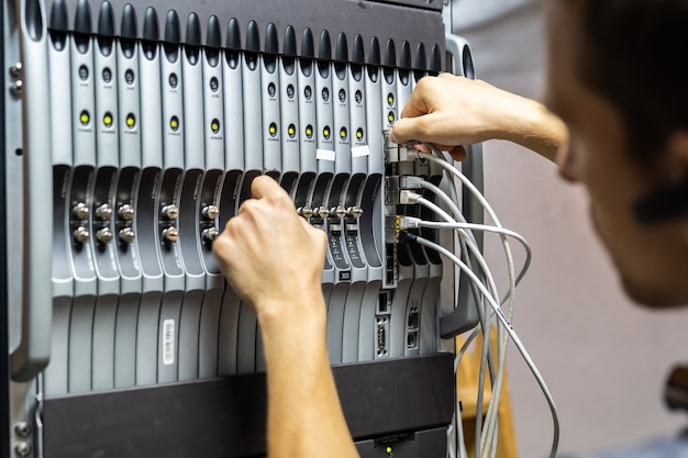 Technician engineer fixing problem with servers and data in cables room Premium Photo