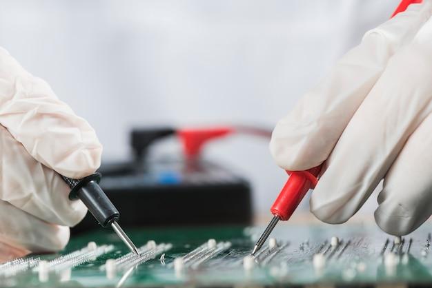 Technician examining computer circuit board with digital multimeter Free Photo