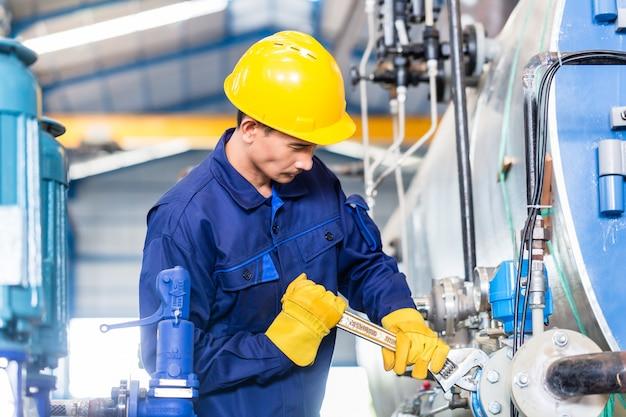 Technician in factory at machine maintenance Premium Photo