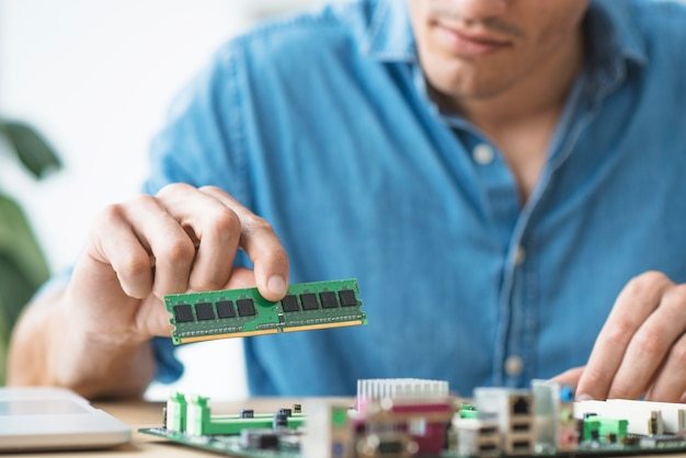 The technician fixing a ram on the socket of the computer motherboard Free Photo