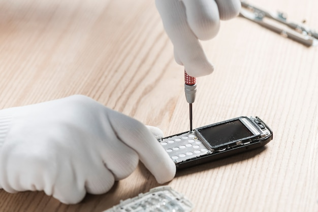 Technician hand repairing cellphone on wooden background Free Photo