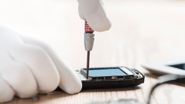 Technician hand repairing mobile phone Free Photo