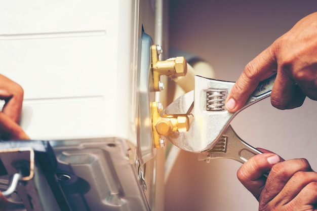 Technician hand using fix wrench to tighten outdoor unit of air condition Premium Photo