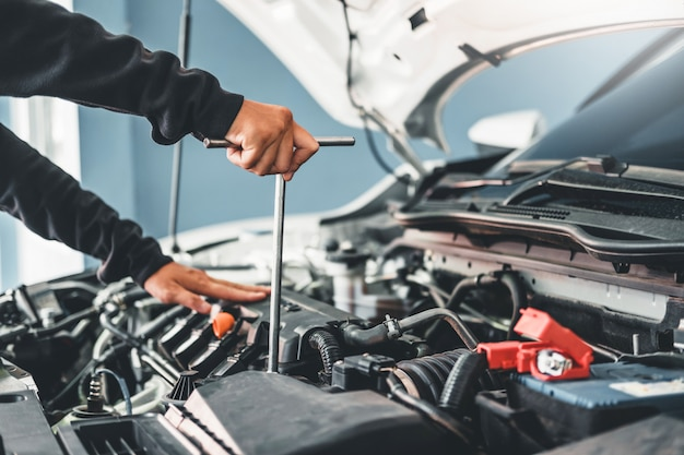 Technician hands of car mechanic working in auto repair Premium Photo