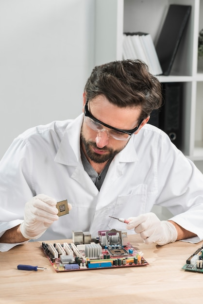 Technician holding computer chip with motherboard on wooden desk Free Photo