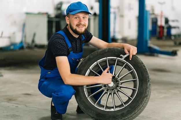 Technician holding wheel at garage Free Photo