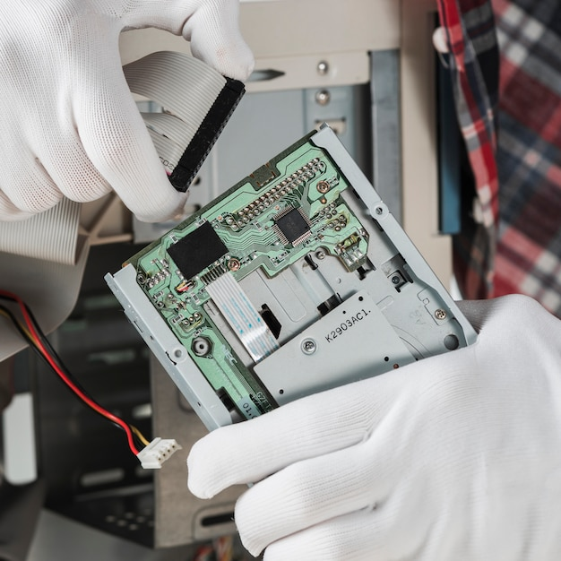 Technician inserting ide computer cable in hard disk drive Free Photo