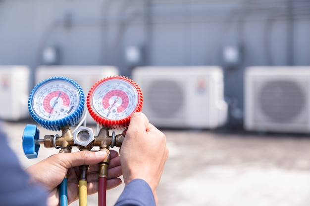 Technician is checking air conditioner, measuring equipment for filling air conditioners. Premium Photo