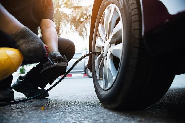 Il tecnico gonfia la gomma dell'auto - concetto di sicurezza del trasporto di servizio di manutenzione dell'automobile Foto Gratuite