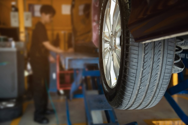 Technician is inflate car tire, car maintenance service transportation safety Free Photo