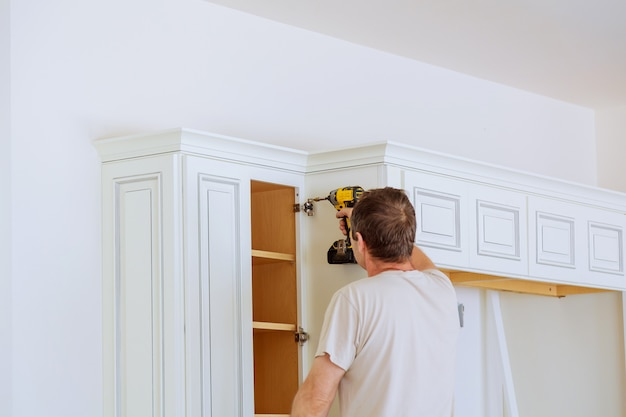 Technician man installing kitchen cabinets Premium Photo
