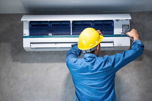Technician man repairing ,cleaning and maintenance air conditioner Premium Photo