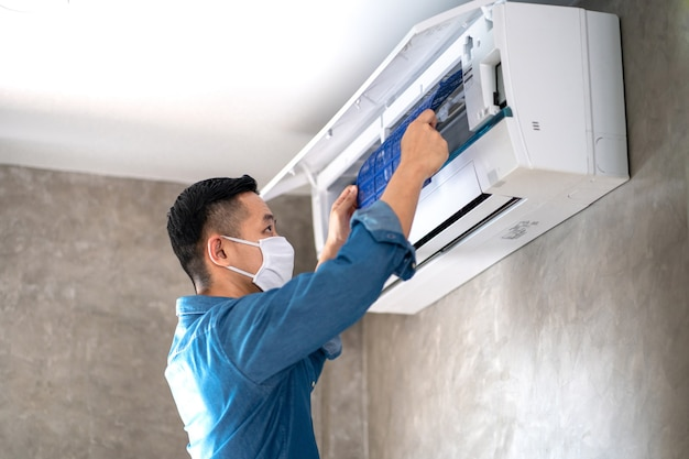 Technician man repairing ,cleaning and maintenance air conditioner Premium Photo