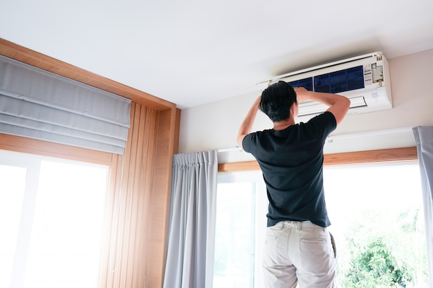 Technician man repairing, cleaning and maintenance air conditioner Premium Photo