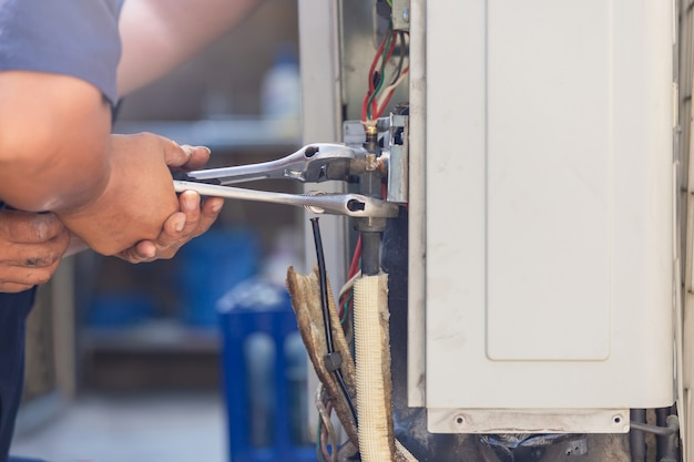 Technician man using a wrench fixing modern air conditioning system, maintenance and repair concept Premium Photo