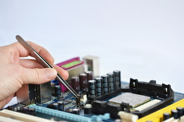 Technician placing a chip with pliers Free Photo