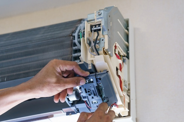Technician repair air conditioner with screwdriver, install electric wires of the air conditioner Premium Photo