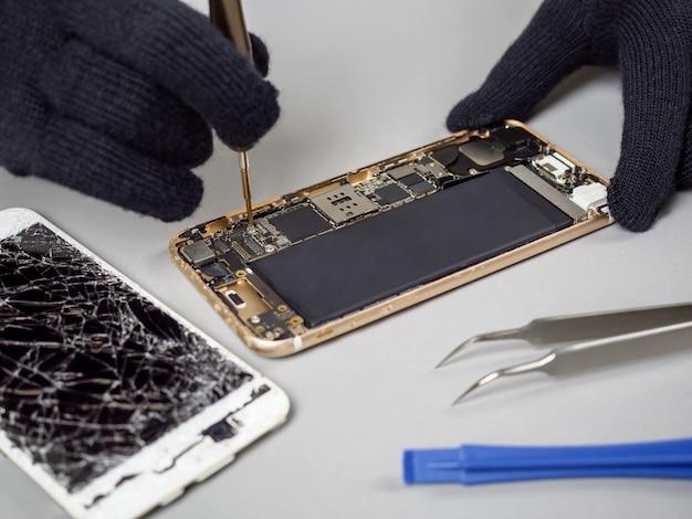 Technician repairing broken smartphone on desk Premium Photo