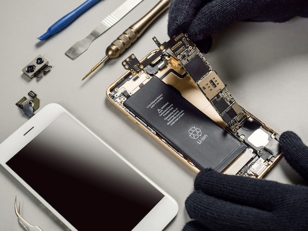 Technician repairing broken smartphone on desk Premium Photo