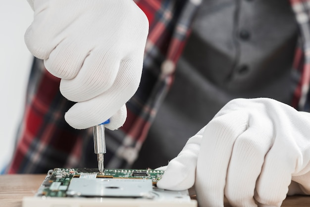 Technician repairing computer motherboard with screwdriver Free Photo
