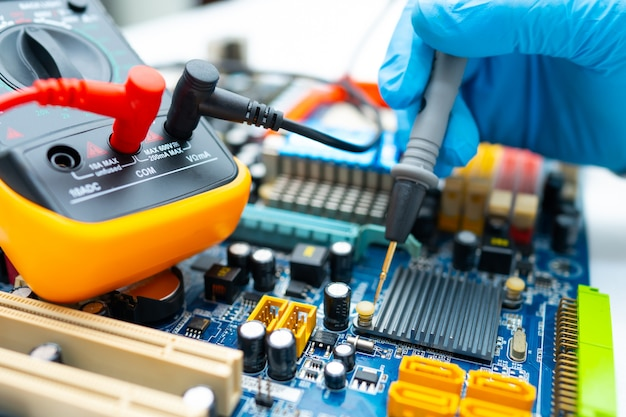 Technician repairing inside of hard disk by multimeter and soldering iron. Premium Photo