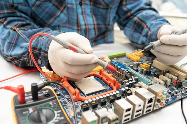 Technician repairing inside of hard disk by soldering iron. Premium Photo