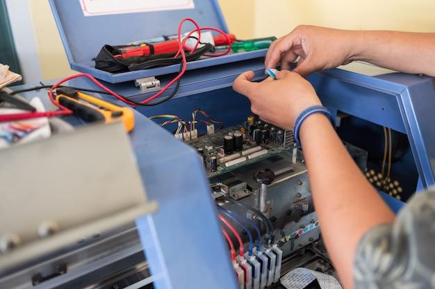 Technician repairing mainboard system of colors dispensers of inkjet printer Premium Photo