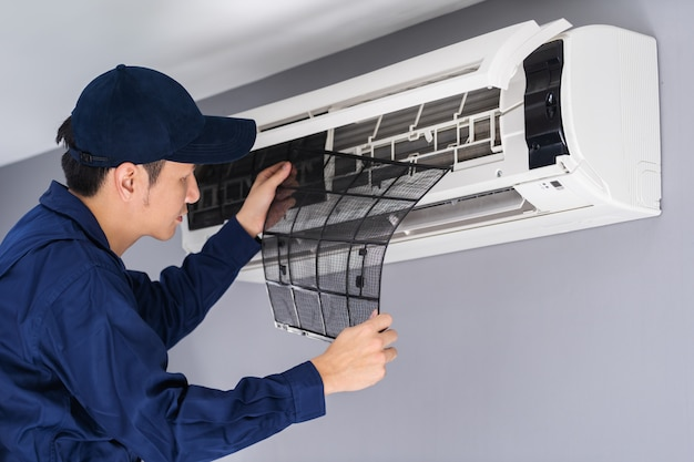 Technician service removing air filter of air conditioner for cleaning Premium Photo