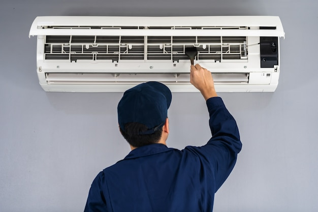 Technician service using brush to cleaning the air conditioner Premium Photo