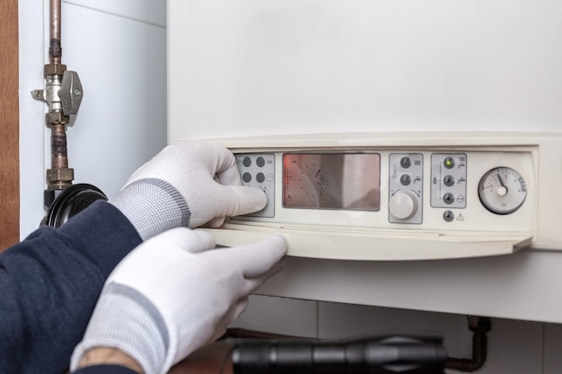 Technician servicing heating boiler in a house. maintenance concept Premium Photo